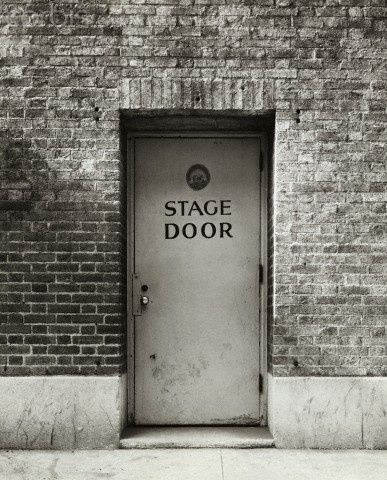 black and white picture of a stage door inset of a brick wall